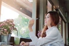 确信的年轻亚裔女实业家画象在她的手上的拿着一支笔在咖啡店有拷贝空间背景 库存照片