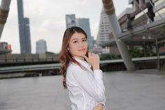 确信的年轻亚裔妇女画象有注视着在照相机的白色衬衣的都市大厦公众背景 库存照片