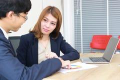 确信的年轻亚裔投资顾问女商人谈论对她的客户 免版税库存照片