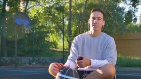 确信的年轻人坐篮球场和听的音乐,看照相机,拿着电话和球,公园  股票录像
