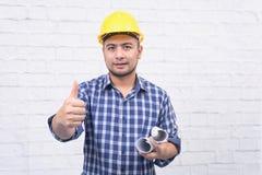 确信的微笑的建筑师在礼服藏品图纸厕所 免版税图库摄影