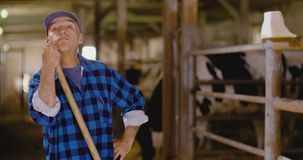 确信的成熟男性农夫藏品干草叉在槽枥 股票录像
