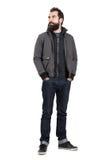 确信的时髦的在看用在口袋的手的戴头巾运动衫的行家佩带的夹克 图库摄影