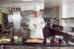 确信的男性厨师用熟食在厨房里 免版税库存图片