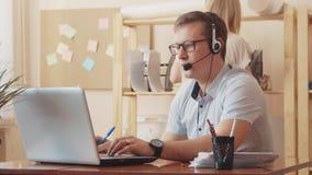 确信的男性客户服务代表画象与耳机的在电话中心 坐在计算机的一个人 股票录像