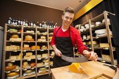 确信的男性推销员切口乳酪画象在商店 免版税库存图片