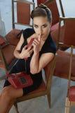 确信的美丽的妇女坐古色古香的红色椅子 免版税库存照片