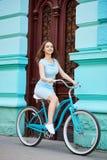 确信的美好的女性通过与红色门的骑马蓝色自行车老蓝色大厦在夏日 免版税库存图片