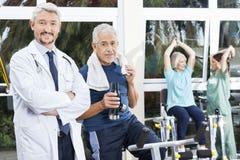确信的老人和医生In Fitness Studio 免版税图库摄影