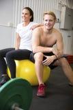 确信的运动员坐在健身俱乐部的锻炼球 库存照片