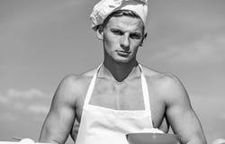确信的面孔的人佩带烹调帽子和围裙,在背景的天空 阳刚之气概念 有裸体的厨师厨师 库存照片