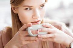 确信的从大杯子的妇女饮用的咖啡 库存图片