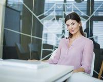 确信的年轻女实业家画象在会议桌上 免版税图库摄影