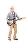 确信资深使用在一把电吉他 免版税图库摄影