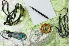 确定移动方向的游人的属性在旅游地图的一次旅行期间使用指南针 免版税图库摄影