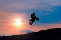 阻碍在日落的摩托车车手的剪影 免版税库存图片