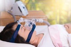 阻碍睡眠停吸疗法,使用CPAP机器的妇女 库存图片