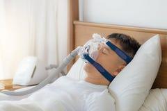 阻碍睡眠停吸疗法,戴着CPAP面具的人 免版税库存照片