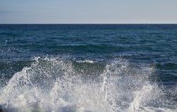 击碎在一个多岩石的海滩和泡沫和喷水的强有力的波浪出现 库存图片