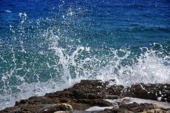 击碎在一个多岩石的海滩的强有力的波浪 免版税库存图片
