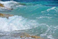 击碎在一个多岩石的海滩的强有力的波浪 图库摄影