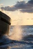 击碎在日落的岩石的波浪 免版税库存照片
