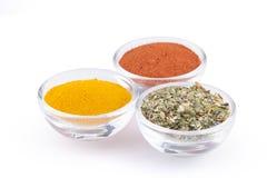 碎姜黄、辣椒粉和意大利草本在白色背景隔绝的玻璃碗 库存图片
