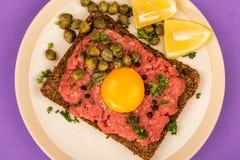 碎牛肉洋葱鸡蛋混合菜用雀跃和一个未加工的鸡蛋 免版税图库摄影