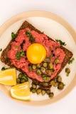碎牛肉洋葱鸡蛋混合菜用雀跃和一个未加工的鸡蛋 免版税库存照片