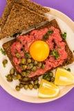 碎牛肉洋葱鸡蛋混合菜用雀跃和一个未加工的鸡蛋 免版税库存图片