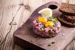 碎牛肉洋葱鸡蛋混合菜用在上面的两个鹌鹑蛋黄 免版税图库摄影