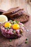 碎牛肉洋葱鸡蛋混合菜用在上面的两个鹌鹑蛋黄 免版税库存图片