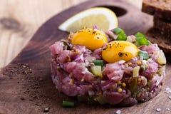 碎牛肉洋葱鸡蛋混合菜用在上面的两个鹌鹑蛋黄 免版税库存照片
