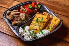 碎玉米粥用肉炖煮的食物猪肉、牛肉和沙拉在塑料盘 街道食物 文本的空位 免版税库存照片