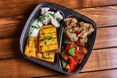碎玉米粥用肉炖煮的食物猪肉、牛肉和沙拉在塑料盘 街道食物 文本的空位 库存照片