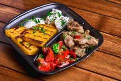 碎玉米粥用肉炖煮的食物猪肉、牛肉和沙拉在塑料盘 街道食物 文本的空位 库存图片