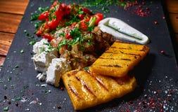 碎玉米粥用肉炖煮的食物猪肉、牛肉和沙拉在黑人委员会 婚姻正餐肉卷熏制的蕃茄 文本的空位 免版税库存图片