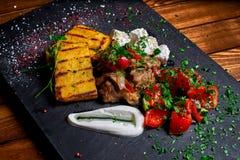 碎玉米粥用肉炖煮的食物猪肉、牛肉和沙拉在黑人委员会 婚姻正餐肉卷熏制的蕃茄 文本的空位 免版税库存照片