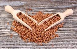 碎荞麦片堆与匙子的木表面上 免版税库存图片