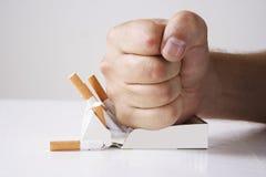 击碎香烟的手 免版税库存图片