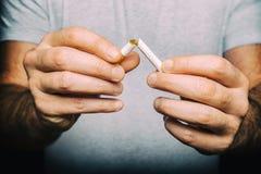 击碎香烟的男性手 免版税库存照片