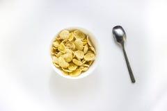 碗与匙子的玉米片在白色背景 库存图片