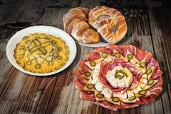 碗与开胃菜美味盘Meze的俄国与芝麻新月形面包在老庭院表上设置的蜗牛卷的沙拉和椒盐脆饼 免版税库存图片