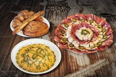 碗与开胃菜美味盘Meze的俄国沙拉和束芝麻新月形面包在老庭院表上供食的油酥点心 图库摄影