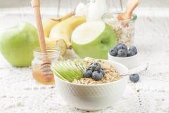 碗与绿色苹果计算机、香蕉、蓝莓、蜂蜜和Chia种子的燕麦粥粥 免版税库存图片