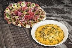 碗俄国沙拉和满盘在老破裂的木庭院表上的开胃菜美味盘Meze 库存照片