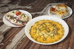碗俄国沙拉用烟肉蛋和乳酪三明治和菠菜乳酪饼在老片状木庭院表上设置的Zeljanica 免版税图库摄影