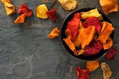 碗健康菜芯片,与拷贝空间的顶视图在黑暗的石头 免版税库存图片