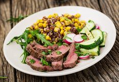 碗午餐用烤牛排和奎奴亚藜、玉米、黄瓜、萝卜和芝麻菜 免版税库存图片