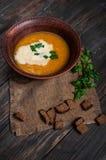 碗南瓜汤用在木桌上的面包油煎方型小面包片 图库摄影